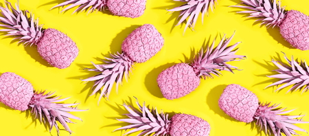 Pink painted pineapples on a vivid yellow background Фото со стока