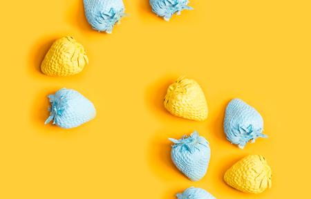 Blauwe en gele geschilderde aardbeien op een gele achtergrond Stockfoto - 79017250