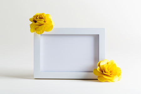 blank spaces: Blank white picture frame with flowers on a white background Stock Photo