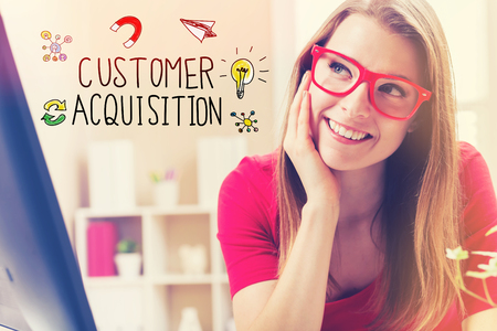 Customer Acquisition text with young woman in her home office Stock Photo