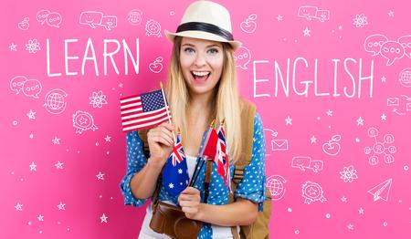 英語圏の国の国旗を持つ若い女性で英語のテキストを学ぶ