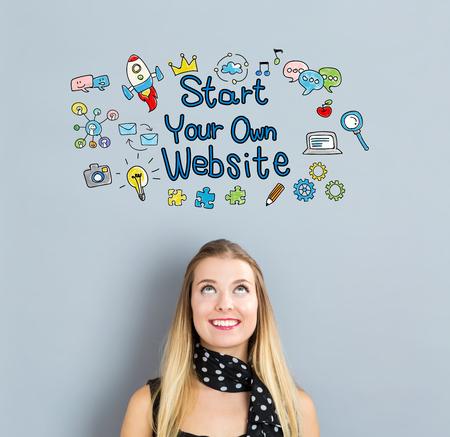 灰色の背景に幸せな若い女とスタート独自のウェブサイトのコンセプト 写真素材