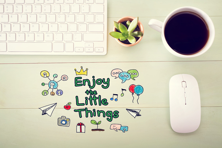 desk light: Enjoy The Little Things concept with workstation on a light green wooden desk Stock Photo