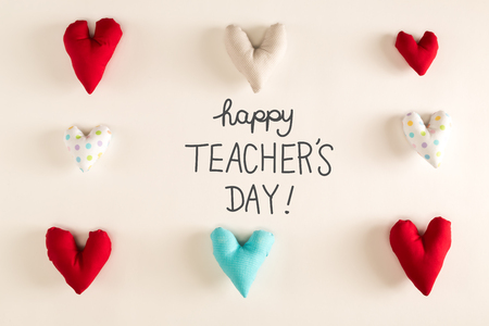 Teachers Day message with blue heart cushions on a white paper background