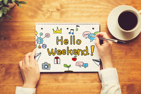 Hallo Weekendtekst met een persoon die een pen op een houten bureau houdt Stockfoto