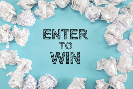 Enter To Win text with crumpled paper balls on a blue background Stock Photo