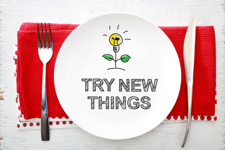 Try New Things concept on white plate with fork and knife on red napkins