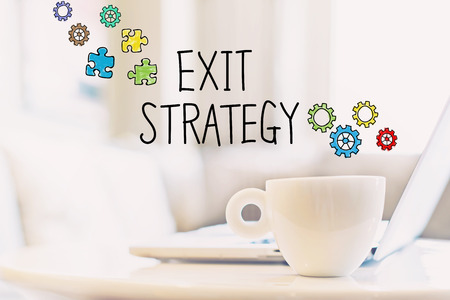Exit Strategy concept with a cup of coffee and a laptop Banco de Imagens