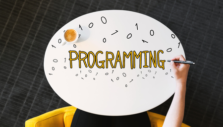Programming text on a white table with person's hand Stock Photo