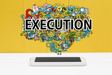 Execution concept with smartphone on yellow wooden background Фото со стока