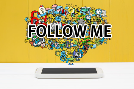 Follow Me concept with smartphone on yellow wooden background