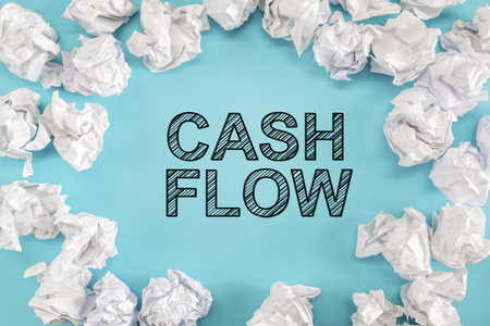 Cash Flow text with crumpled paper balls on a blue background