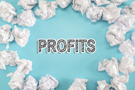 Profits text with crumpled paper balls on a blue background