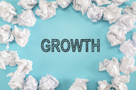 Growth text with crumpled paper balls on a blue background