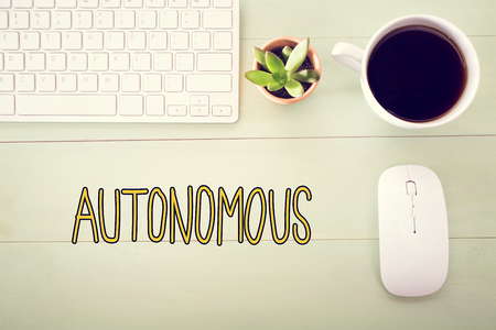 Autonomous concept with workstation on a light green wooden desk Stock Photo