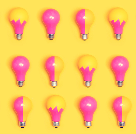 Colored light bulbs aligned on a yellow background Stock Photo