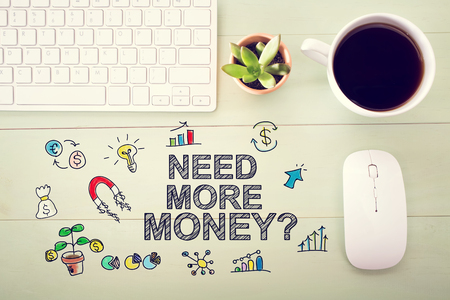Need More Money concept with workstation on a light green wooden desk Reklamní fotografie