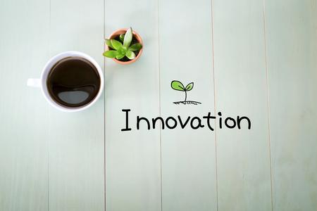 パステル グリーンの木製のテーブルにコーヒーのカップを持つイノベーション コンセプト