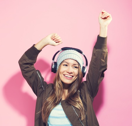 Happy young woman with headphones on a pink background Imagens