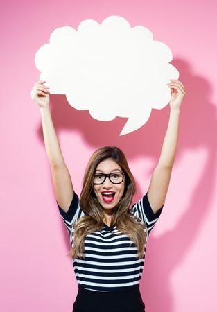 Jeune femme tenant une bulle de dialogue sur un fond rose Banque d'images - 79856684