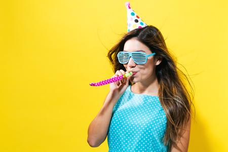 Noisemaker 노란색 배경에 파티 모자와 젊은 여자 스톡 콘텐츠 - 79856691