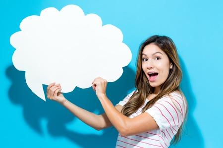 Jonge vrouw die een toespraakbel op een blauwe achtergrond houdt