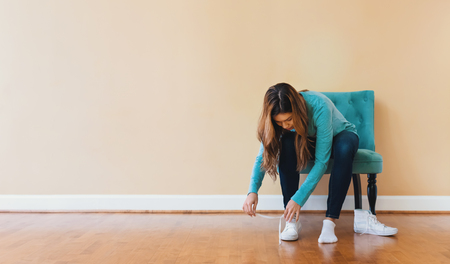 Young latina woman tying her shoes in a large interior room Stock Photo