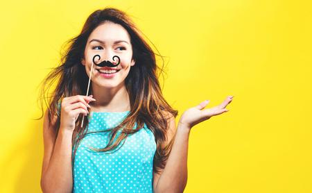 Jonge vrouw die papier partij stokken op een gele achtergrond Stockfoto