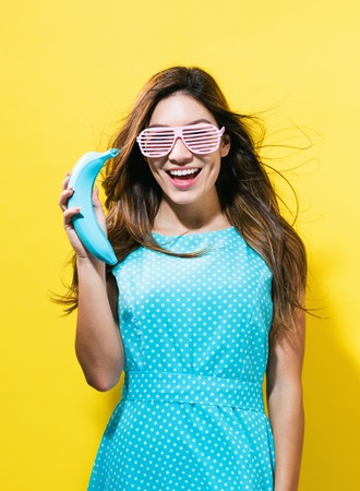 Happy young woman holding a colored banana on a yellow background Imagens