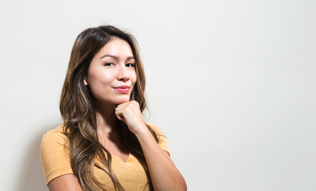 Young woman in a thoughtful pose on a off white background