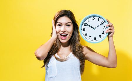 イエロー バック グラウンドで時計を保持している若い女性