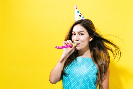 Young woman with party hat with noisemaker on a yellow background
