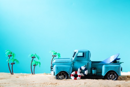 Miniature blue truck with surfboard and buoy on a bright blue background Stock Photo