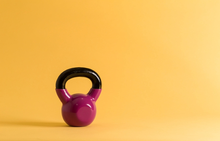 Pink cast iron kettlebell on a yellow background