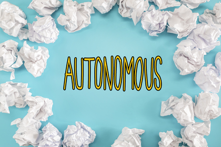 Autonomous text with crumpled paper balls on a blue background Stock Photo