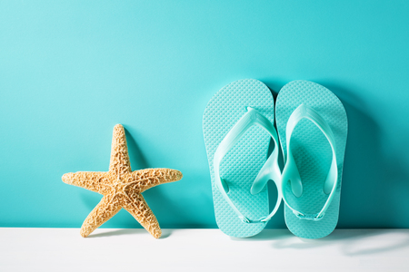 Summer theme with sandals and starfish on a bright blue background Stock Photo - 81698925