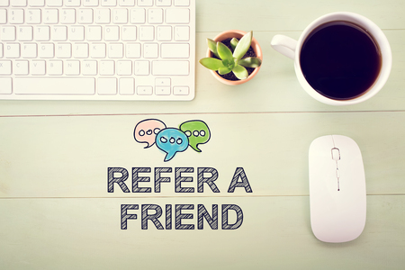 Refer A Friend concept with workstation on a light green wooden desk