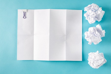 Blank paper with crumpled paper balls on a blue background