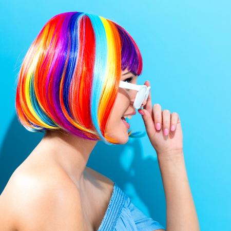 Mooie vrouw in een kleurrijke pruik op een blauwe achtergrond Stockfoto