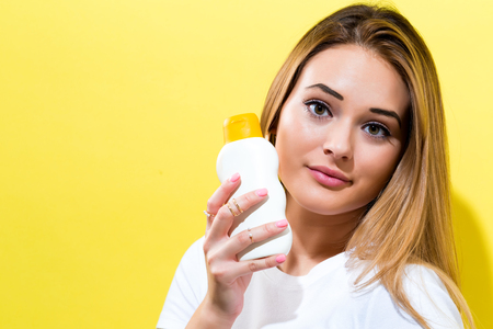Young woman a bottle of sunblock on a yellow background Stock Photo