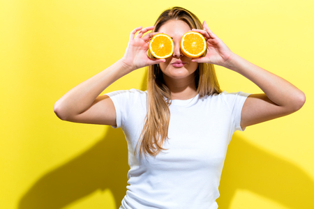 Happy young woman holding oranges halves on a yellow background Foto de archivo