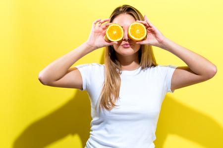 Gelukkige jonge vrouw die sinaasappelen houdt helften op een gele achtergrond