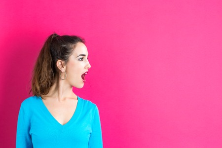 Profile of a young woman on a pink background
