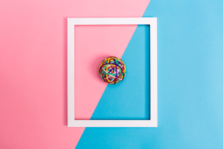 Rubber band ball with frame on a bright split tone background Stock Photo