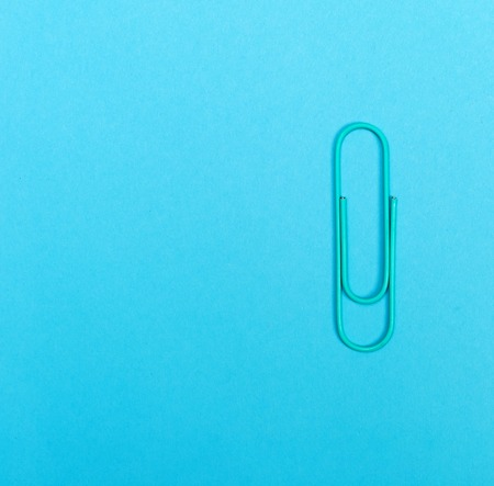 Paper clip on a vivid blue paper background Stock fotó