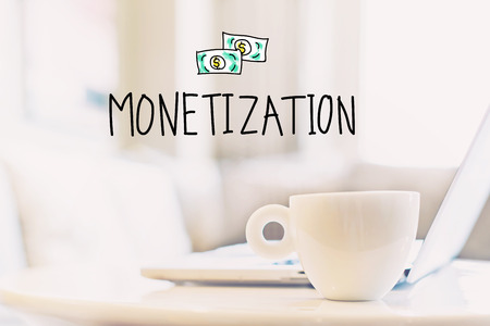 Monetization concept with a cup of coffee and a laptop Stock fotó