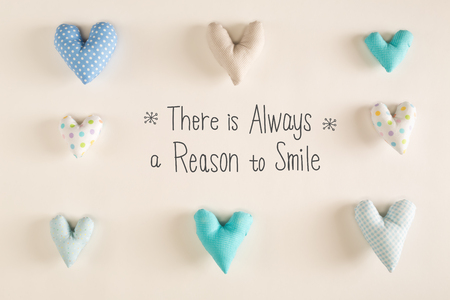 There Is Always A Reason to Smile message with blue heart cushions on a white paper background