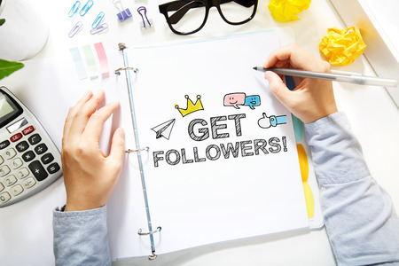 Person drawing Get More Followers concept on white paper in the office