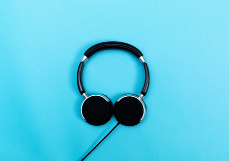 Pair of black headphones on a blue background Фото со стока - 80701960