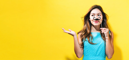 pretending: Young woman holding paper party stick on a yellow background Stock Photo